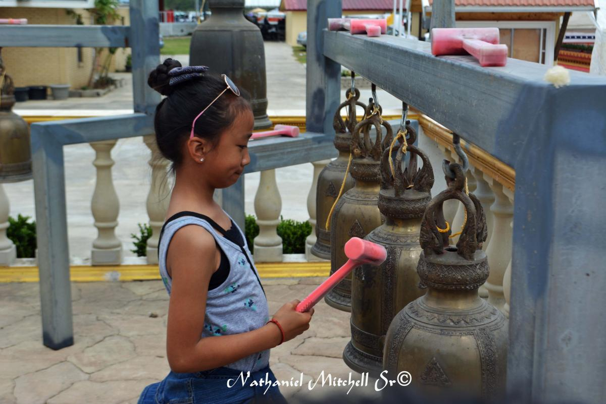 Child rings the bells at Lao Temple in Coteau