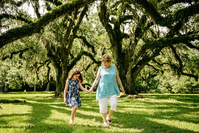 Woman and girl walk hand in hand under live oaks at Jungle Gardens of Avery Island
