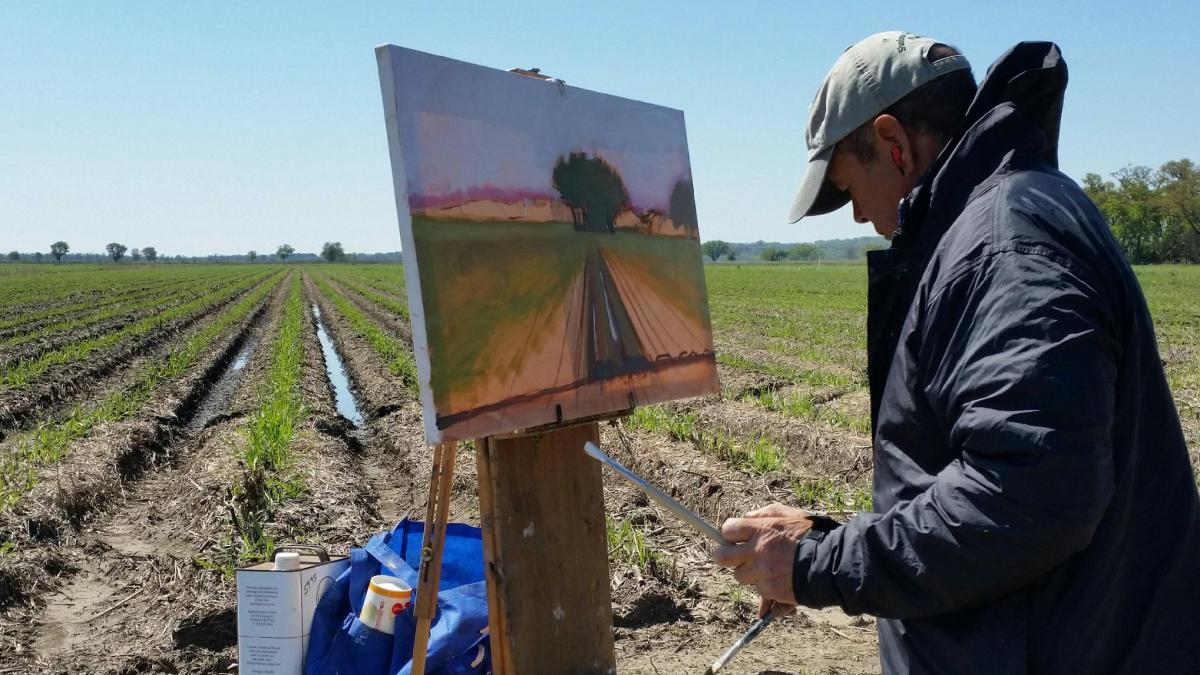 Shadows on the Teche Plein Air competition artist painting in a field