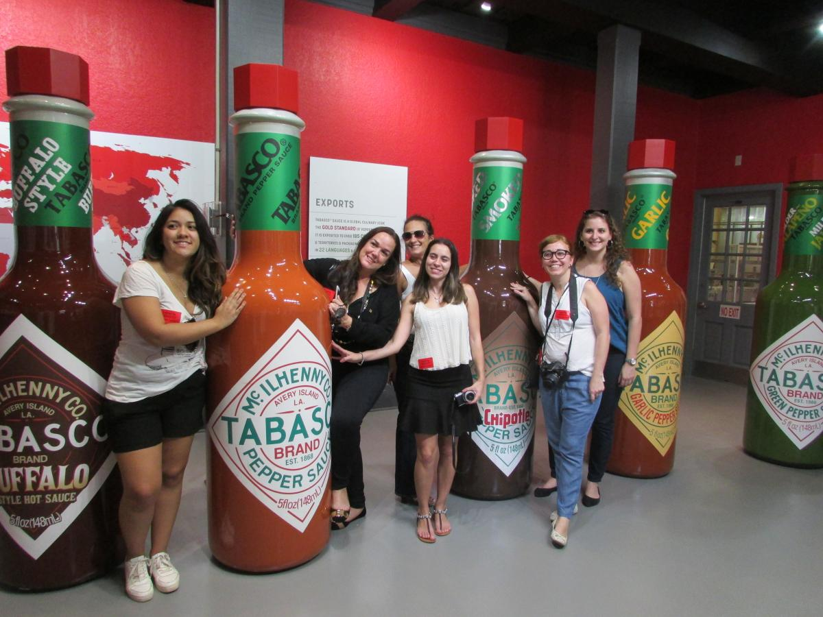 tourists pose in front of tabasco bottles at new museum